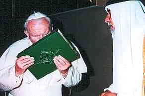 Pope John Paul II Kisses the Koran while meeting with an official in Iraq on May 14, 1999